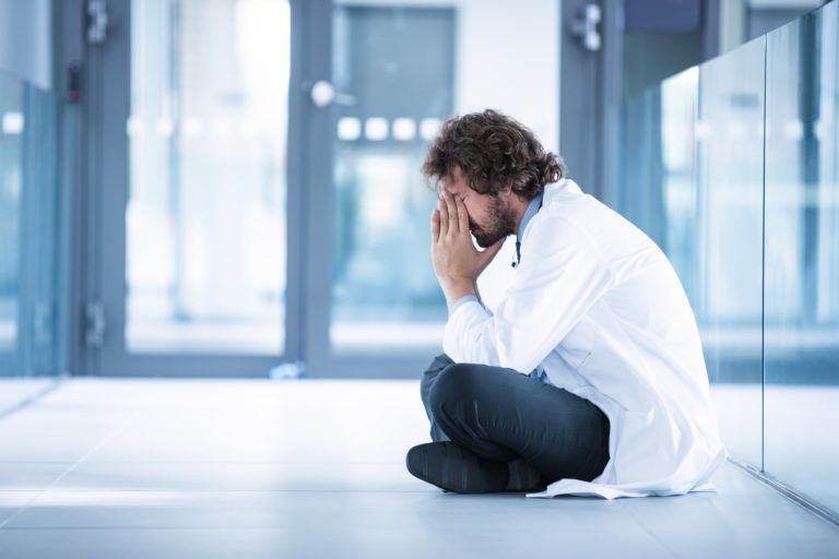 Worried doctor sitting on floor